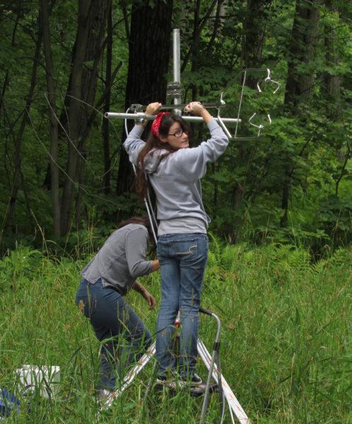 woman sets up an antenna-like sensor