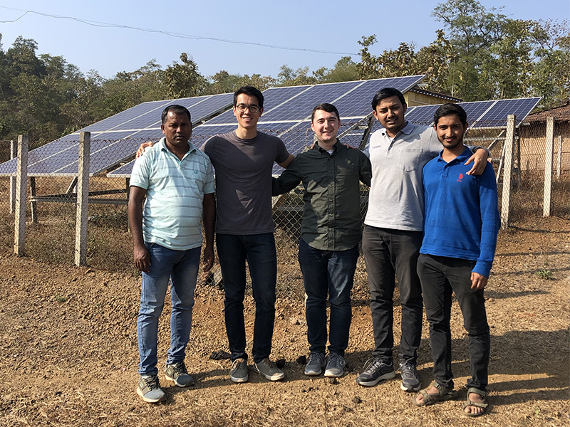 group of people in india in front of solar panels