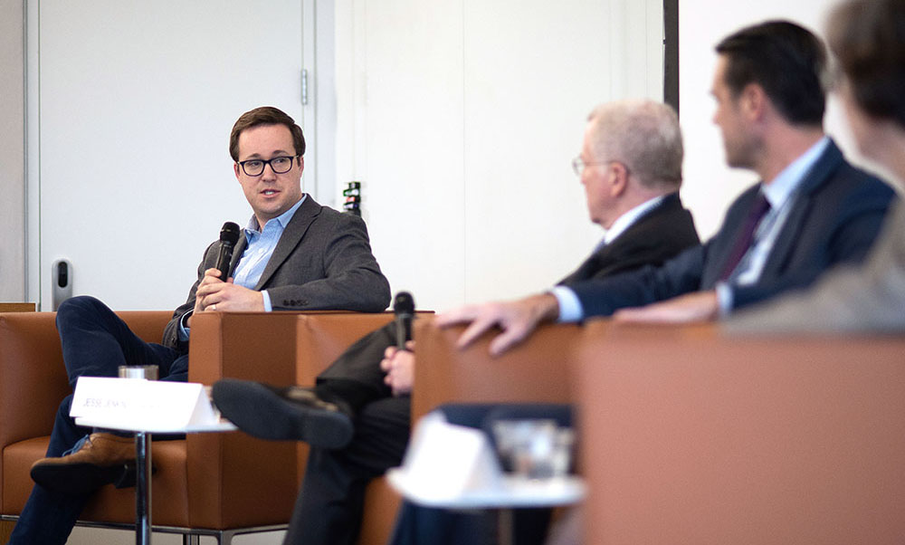 Man sitting with microphone talks to a panel of people.